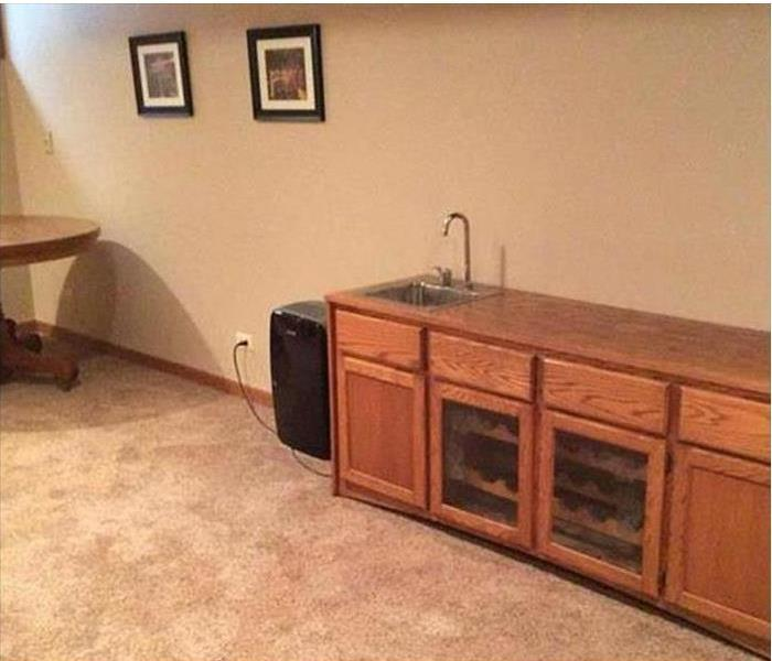 water soaked into carpet and walls, cabinet with sink